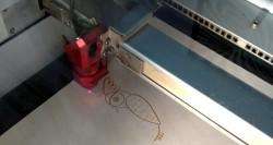 Découpe laser en train de graver un hibou sur du bois 3mm.